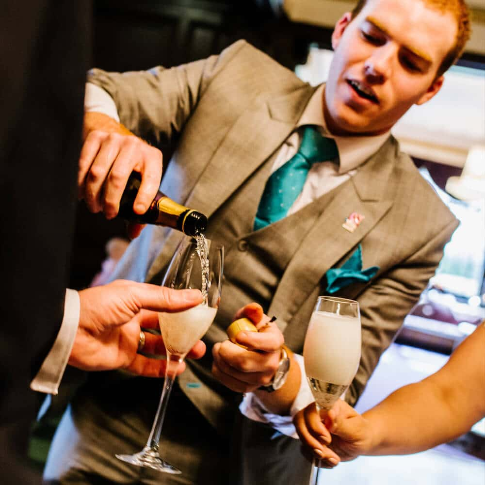 manchester wedding magician sam fitton pours champagne for bride and groom at eaves hall